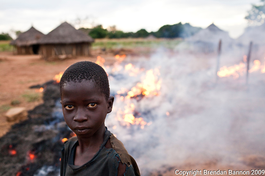 A child standing before a  crop burn in Madi Opei, northern Uganda. the area is populated with people displaced by the decades long conflict with the Ugandan rebel group the  Lord's resitance Army.