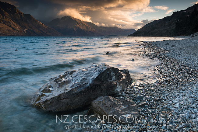 Dramatic sunset over Lake Wakatipu with surrounding mountains, Central Otago, New Zealand