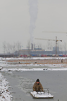 A woman harvests lotus roots from a frozen lake against a backdrop of a factory on the outskirts of Beijing, China on March 8, 2010. (Canon 7D, 70-200mm f 2.8)