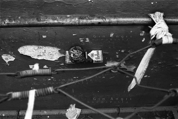 Una brandina in una cella dell'ex carcere San Donnino di Como, Mensola costruita con pacchetti di sigarette. Mozziconi.
