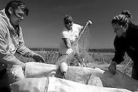 A female crew unravel their gill net twisted by surf in bad weather.  They attached a buoy underneath plywood and spin the whole container to fix their net quickly.