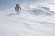 A winter hiker ascending the Air Line Trail in extreme weather conditions in the White Mountains, New Hampshire USA during the winter months.