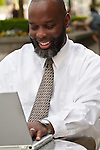 African American man with laptop looking happy