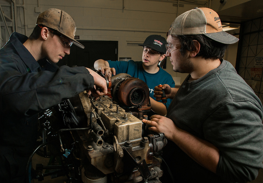 Diesel Power Technology students Zack Austin, left, Bailey Sperling, center, and Nicholas Kough, right, take apart a diesel engine during class in UAA's Auto Diesel Technology Building.