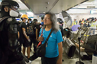 CHINA, Hong Kong: 21 August 2019 <br /> A member of the general public walking through Yuen Long train station stares at a protester during clashes with riot police after the train station was filled with protesters angry about the Yuen Long attack which happened exactly one month ago.  <br /> The attack, on 21st of July, was by approximately 100 men who violently attacked protesters, reporters and a pregnant woman. No arrests were made and it is believed the gang were colluding with the police.<br /> Rick Findler / Story Picture Agency