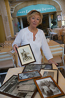 """Europe/Provence-Alpes-Côte d'Azur/83/Var/Saint-Tropez: Simone Durckstein  propriétaire de l'Hotel Restaurant """"La Ponche"""" contemple les photos de l'histoire de  l'Hôtel avec des vedetets de cinéma dont Brigitte Bardot"""