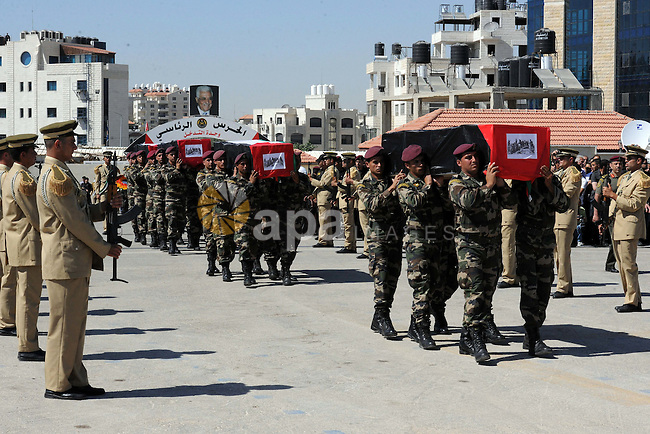 Members of the Palestinian security forces carry flag-covered coffins containing the remains of Palestinian militants during an official ceremony in the West Bank city of Ramallah May 31, 2012. The remains of 91 Palestinian militants whose attacks  Israel were returned to the West Bank and Gaza on Thursday in a gesture Israel said it hoped could help revive peace efforts. Photo by Thaer Ganaim