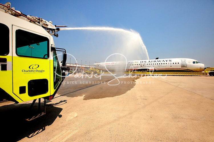Arriving beneath a spray from a firetruck's hose, US Airways Flight 1549, also known as the Miracle on the Hudson plane, traveled in pieces to its final resting place at the Carolina Aviation Museum in Charlotte, NC.  Two years earlier, the commercial passenger flight was enroute to Charlotte/Douglas International Airport when it was successfully landed in New York's Hudson River after striking a flock of Canada Geese six minutes after taking off from LaGuardia Airport.