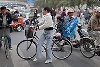 A woman ferries her daughter on a bicycle through a busy street in Shanghai, China on November 05, 2009.