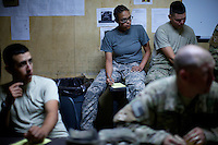 US ARMY Specialist Kahaya Komar ( sitting in background  with glasses)  listens to a mission brief before a day long logistical mission at  Forward Operating Base Fenty in the outskirts of Jalalabad, Afghanistan on Wednesday  May 1, 2010...Specialist Komar is a radio operator and assistant gunner on logistical convoys with Destro Platoon, Fury Company, 2nd Battalion, 4th Brigade, Task Force Mountain Warrior, 4th Infantry Division..