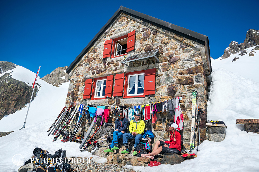 A group of friends sit outside theTrift Hut amongst ski gear drying in the sun, while on a ski tour of the Berner Haute Route, Switzerland