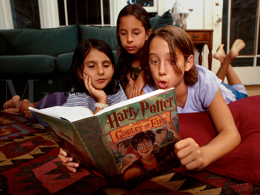 Three girls read a Harry Potter book - Harry Potter and the Goblet of Fire. Older girl, a teenager, reads to the younger ones. Anda Clark, Nina, and Anna. Venice, California.
