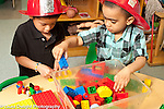 Education Preschool 3 year olds two boys wearing dressup fire hats playing with plastic duplo colored bricks