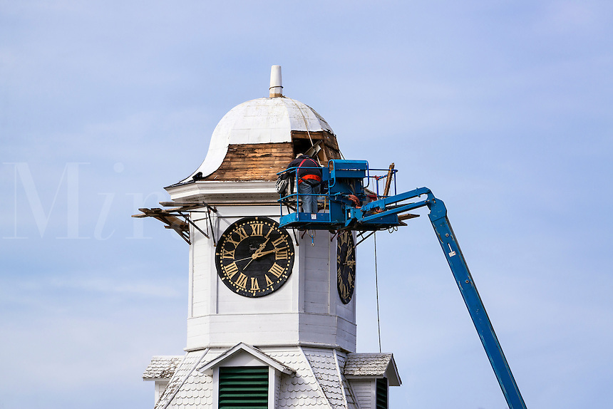 Men on a cherry picker repair the restore the roof of the town clock tower, Weston, Vermont, USA