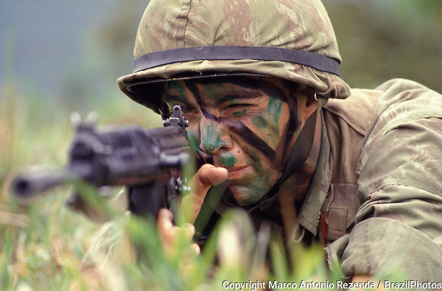 Soldier aiming and shooting, Army, camouflage, disguise, arm, machine-gun, helmet, body-painting, to aim weapon, to attack, attacking, to shoot, to kill, war, warfare.