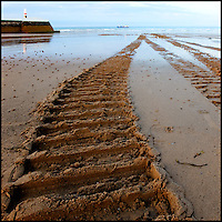 Tyre track in the sand down to the sea, from lifeboat launch
