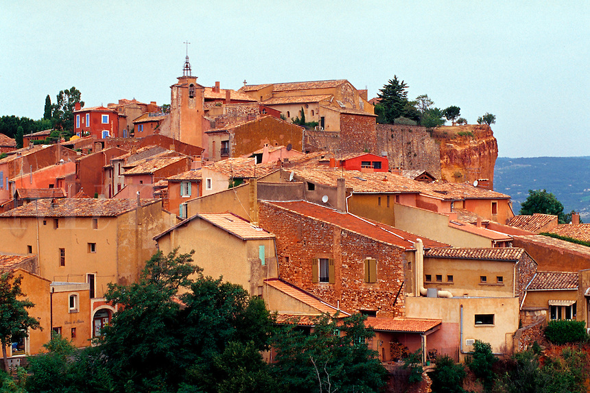 Overview of the roofline of an old French village whose buildings are constructed of ochre stucco. Rousillon, France.