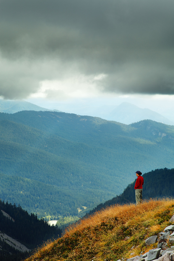 Woman overlooking mountains and valley, Stevens Ridge, Mount Rainier National Park, Washington, USA