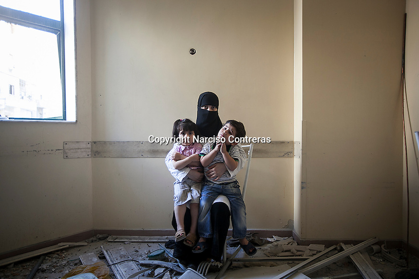 Fatimah, twenty-six-year-old, poses for a photo with her two children, Rashed and Omar, inside an empty ward damaged by shelling at the 4th floor of the Dar Al-Shifa hospital in the rebel-controlled area of Aleppo. September 27, 2012.