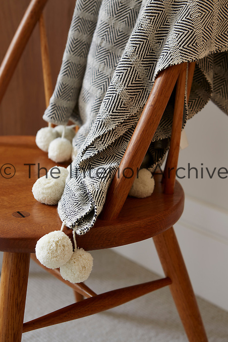 A grey and off-white throw rests on the back of a traditional wood chair.