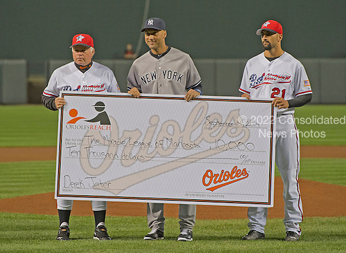 New York Yankees shortstop Derek Jeter (2), center, is presented a check for $10,000.00 by Baltimore Orioles manager Buck Showalter (26), left, and right fielder Nick Markakis (210, left, prior to the game at Oriole Park at Camden Yards in Baltimore, MD on Sunday, September 14, 2014.  The check presentation was part of a pre-game ceremony honoring Jeter.<br /> Credit: Ron Sachs / CNP<br /> (RESTRICTION: NO New York or New Jersey Newspapers or newspapers within a 75 mile radius of New York City)
