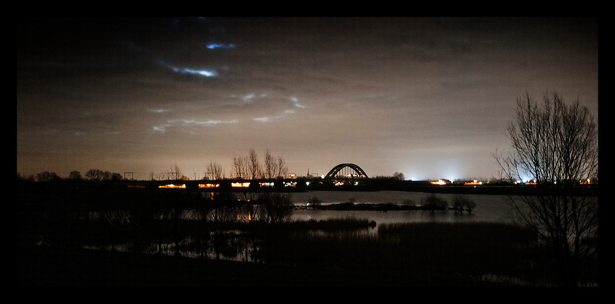 Nederland, Culemborg, 14 jan 2012.Brug bij Culemborg in de nacht, uiterwaarden van de Lek op de voorgrond. Een trein trekt een lichtspoor over de brug .Foto (c): Michiel Wijnbergh..Bridge at Culemborg in the night, floodplains of the river Lek in the foreground.