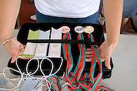 Volunteer holding tray of award medals and ribbons. Special Olympics U of M Bierman Athletic Complex. Minneapolis Minnesota USA