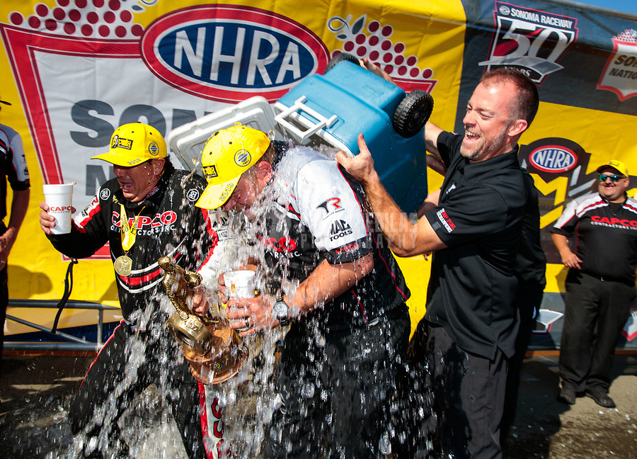 Jul 28, 2019; Sonoma, CA, USA; A crew member for NHRA top fuel driver Billy Torrence is dunked with a cooler of ice water as the team celebrates after winning the Sonoma Nationals at Sonoma Raceway. Mandatory Credit: Mark J. Rebilas-USA TODAY Sports