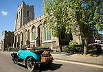 Classic veteran car passing Church of Saint Peter, Sudbury, Suffolk, England