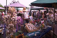 Artisan selling Garlic and Flowers at the Saturday Market in Ganges, on Saltspring Island, in the Southern Gulf Islands of British Columbia, Canada
