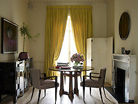 In the drawing room a walnut table is paired with André Arbus chairs
