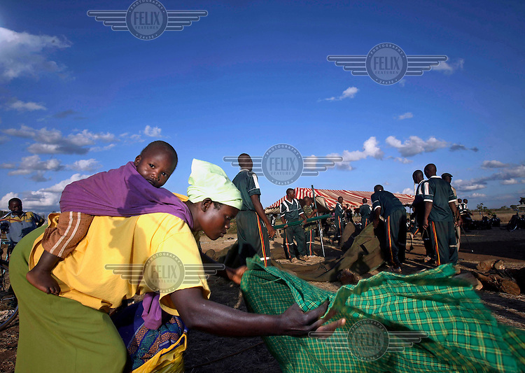 A woman and baby pack up as they and other internally displaced persons (IDPs) camping in the compound of the Prison College in Ruiru are told to go home. Trainees of the college are removing the makeshift shelters to make sure the displaced will move back to their homes, which they had fled following protests against disputed election results which led to unrest and violence.