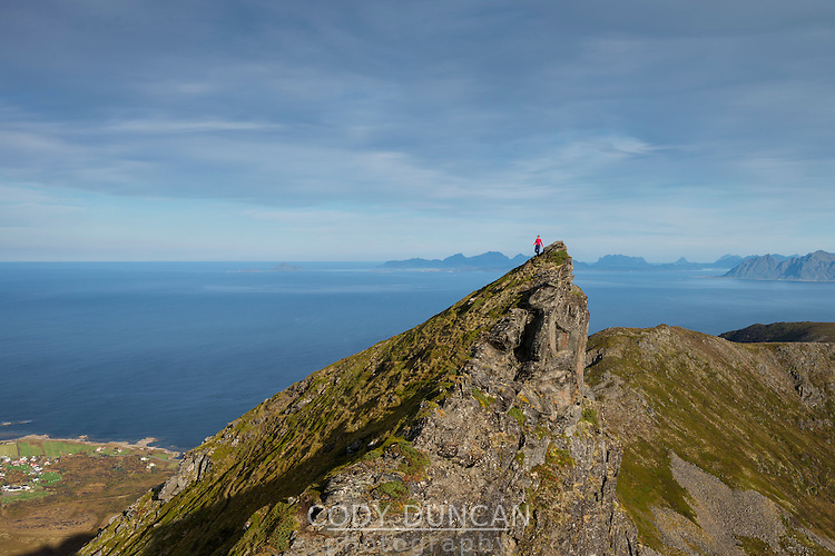 Female hiker descends steep ridge on route to Matmora mountain peak, Austvågøy, Lofoten Islands, Norway