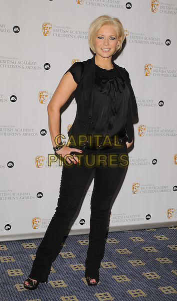 SUZANNE SHAW.Pressroom at the The British Academy Children's Film and Television Awards, London, Hilton Hotel, Park Lane, London, England..November 30th, 2008.BAFTA BAFTA's press room full length black top blouse bow jeans denim brown belt leopard print shoes jacket cap sleeves open toe hands on hips.CAP/CAN.©Can Nguyen/Capital Pictures.