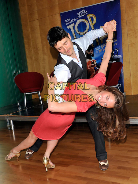 TOM CHAMBERS & SUMMER STRALLEN .Photocall to Launch a new production of 'Top Hat the Musical' at Milton Keynes Theatre, Bucks, UK, May 6th 2011..full length red sleeveless dress dancing pose waistcoat suit blue shirt  beige nude christian louboutin shoes heels  pink grey gray .CAP/JIL.©Jill Mayhew/Capital Pictures