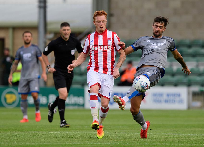 Lincoln City's Ellis Chapman vies for possession with Stoke City's Nathan Collins<br /> <br /> Photographer Chris Vaughan/CameraSport<br /> <br /> Football Pre-Season Friendly - Lincoln City v Stoke City - Wednesday July 24th 2019 - Sincil Bank - Lincoln<br /> <br /> World Copyright © 2019 CameraSport. All rights reserved. 43 Linden Ave. Countesthorpe. Leicester. England. LE8 5PG - Tel: +44 (0) 116 277 4147 - admin@camerasport.com - www.camerasport.com