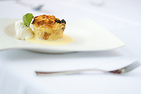 a Plate of Creme Brulee in a plate of cream and whipped cream on a white table with place setting. Fine Dining Environment