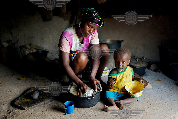 A woman prepares a meal with her child sitting beside her at her home in the village of Nyonken. /Felix Features
