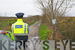 Murder Scene : A garda stands on duty at the entrance to Tullamore bog where the murder victim's body was found.