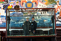 Bolivian Navy officers pose for a portrait behind a fish tank at the naval school in La Paz. Bolivia lost what is now northern Chile in a war over nitrates leaving Bolivia without access to the ocean.