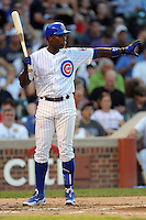 Chicago Cubs left fielder Alfonso Soriano #12 signals for the runner to stay at third on a wild pitch during a game against the Miami Marlins at Wrigley Field on July 17, 2012 in Chicago, Illinois. The Marlins defeated the Cubs 9-5. (Tony Farlow/Four Seam Images).