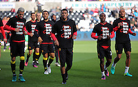 Watford players wearing Show Racism the Red Card t-shirts before the Premier League match between Swansea City and Watford at The Liberty Stadium on October 22, 2016 in Swansea, Wales, UK.