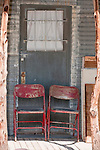 Two metal red chairs on a porch, Nelson, Nev.