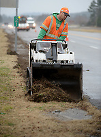 NWA Democrat-Gazette/ANDY SHUPE<br /> Joel Houck, a worker with the Arkansas Department of Transportation, uses a mini track loader Wednesday, Feb. 6, 2019, as he and crew members remove grass that has grown over the sidewalk alongside the Fayetteville Municipal Airport. The sidewalks have long been covered by grass, prompting the work to clear them.