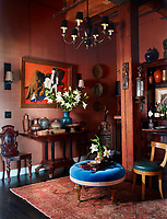 A painting by Edward Ulreich hangs in the entry hall above a Swedish table bought on 1stdibs, the vintage Dutch chandelier and English mahogany chair were found at flea markets, as was the ottoman, re-covered in a velvet by Clarence House, with trim by Samuel & Sons; the sconces are by Restoration Hardware, and the walls are covered in a silk burlap by Donghia.
