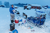 Sarah Stokey packs her sled and snacks her dogs as she readies to leave the Kaltag checkpoint on Monday morning March 11th during the 2019 Iditarod Trail Sled Dog Race.<br /> <br /> Photo by Jeff Schultz/  (C) 2019  ALL RIGHTS RESERVED