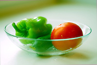 Vegetables on a glass plate: ripe red tomato, green pepper and cucumber