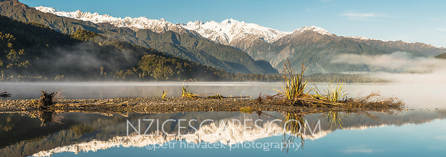 Southern Alps and Mount Tasman reflecting in Lake Mapourika near Franz Josef Glacier on winter morning, Westland Tai Poutini National Park, West Coast, UNESCO World Heritage Area, New Zealand, NZ