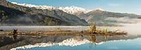 Southern Alps and Mount Tasman reflecting in Lake Mapourika near Franz Josef Glacier on winter morning, Westland Tai Poutini National Park, West Coast, UNESCO World Heritage Area, New Zealand, NZ