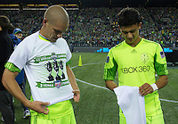 Seattle Sounders FC players Osvaldo Alonso, left and Fredy Montero put on their championship t-shirts after play between the Seattle Sounders FC and the Chicago Fire in the U.S. Open Cup Final at CenturyLink Field in Seattle Tuesday October 4, 2011. Seattle won the game 2-0 to win its third U.S. Open Cup.
